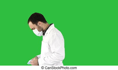 Walking doctor putting on mask and cap on a Green Screen, Chroma Key.