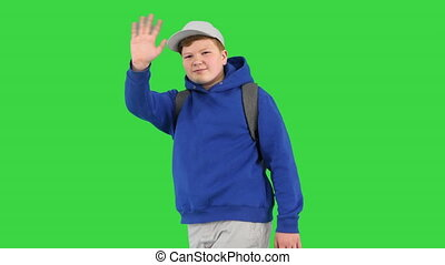 Boy walking by and making hello gesture to camera on a Green Screen, Chroma Key.