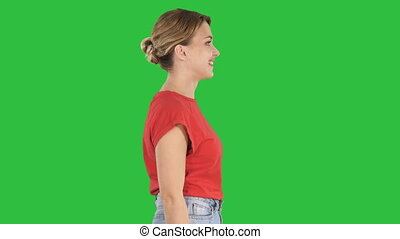 Walking woman in in jeans and t-shirt on a Green Screen, Chroma Key.