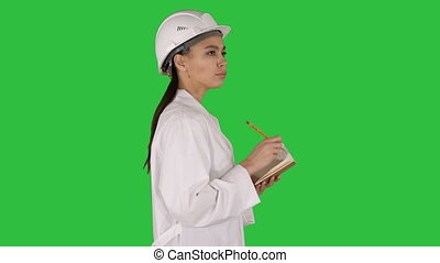 Woman engineer with helmet is holding pen and checklist...