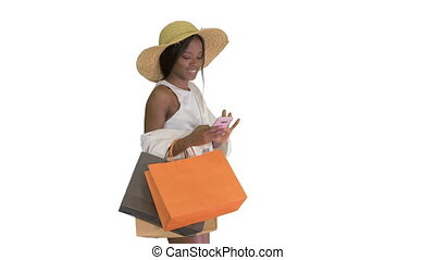 Medium shot. Side view. Woman in summer outfit using mobile walking on white background. Professional shot in 4K resolution. 4151. You can use it e.g. in your commercial video, business, presentation, broadcast