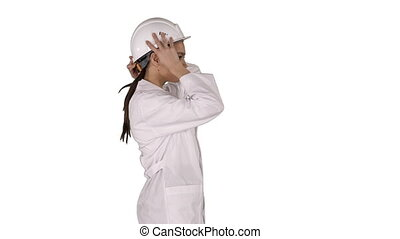 Woman in white robe putting hard hat on while walking on ...