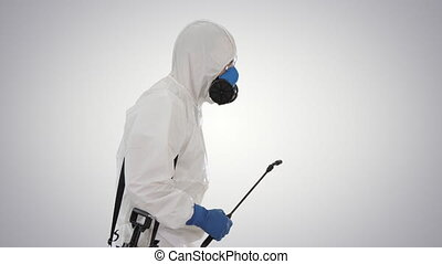 Medium shot. Side view. Worker in Hazmat Suit and Face Protection Mask Walking With Disinfection Equipment on gradient background. Professional shot in 4K resolution. 53. You can use it e.g. in your medical, commercial video, business, presentation, broadcast