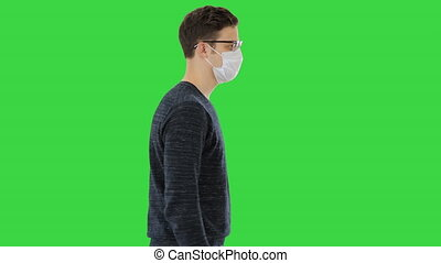 Young handsome man walking with medical mask on on a Green Screen, Chroma Key.