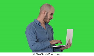 Young middle eastern businessman, standing and typing on...