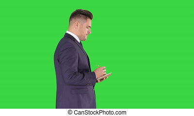 Young positive caucasian businessman walking and making checklist on a Green Screen, Chroma Key.