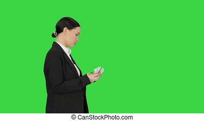 Medium shot. Side view. Young woman in a suit counting money on a Green Screen, Chroma Key. Professional shot in 4K resolution. 043. You can use it e.g. in your medical, commercial video, business, presentation, broadcast