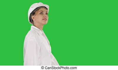Young woman in hard hat walking and looking around on a Green Screen, Chroma Key.
