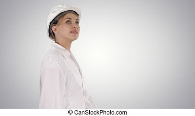 Young woman in hard hat walking and looking around on ...