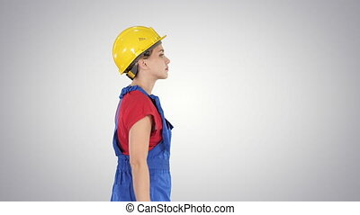 Young woman in yellow hardhat walking on gradient...