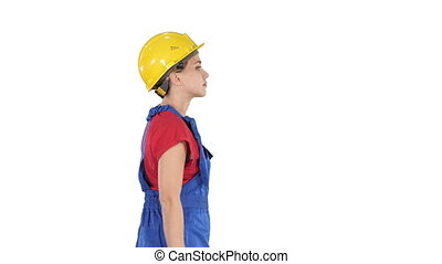 Young woman in yellow hardhat walking on white background. -...