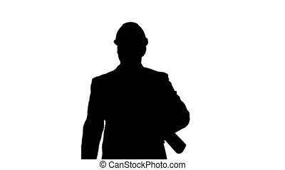 Silhouette Male architect in a suit and hard hat walking ...