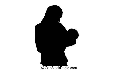 Silhouette Mother gives baby to drink from bottle.