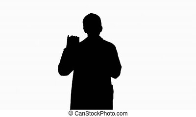 Medium shot. Silhouette Walking Male Doctor showing empty white box of pills. Professional shot in 4K resolution. 4151. You can use it e.g. in your commercial video, business, presentation, broadcast