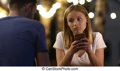 Bored beautiful young woman on bad date using her phone.