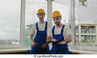 Builders funny dance in helmets.