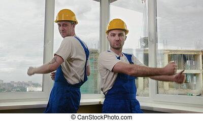 Construction Workers dancing in helmets.
