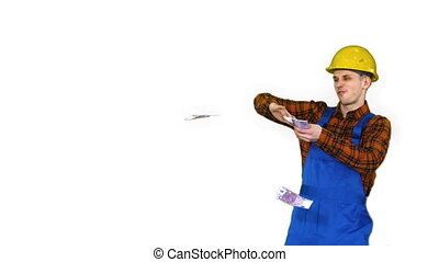 Costruction worker in yellow hard hat throwing money in the ...