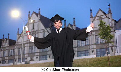 Male student in academic gown dancing.