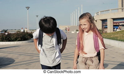 Medium shot. Slow motion. Schoolchildren with backpacks walking and having fun. Professional shot in 4K resolution. 34. You can use it e.g. in your commercial video, medical, business, presentation, broadcast
