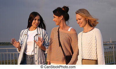 Happy female friends walking and loughing while one is ...
