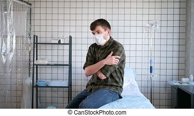 Young man wearing protective mask sitting alone in the hospital chamber waiting for tests results, coronavirus isolation.