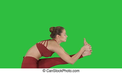 Sporty beautiful blond young woman in sportswear doing Utthita Hasta Padangushthasana on a Green Screen, Chroma Key.