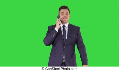 Successful man in suit speaks on phone and walks on a Green Screen, Chroma Key.