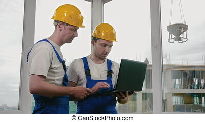 Two builders wearing protective helmets working on a laptop.