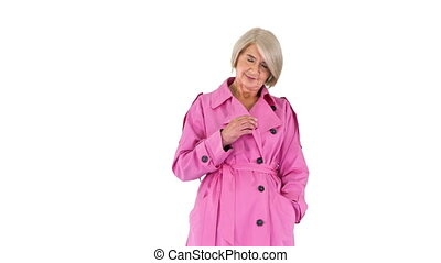 Medium shot. Walking in and out of the frame. Beautiful senior lady in pink autumn outfit on white background. Professional shot in 4K resolution. 063. You can use it e.g. in your medical, commercial video, business, presentation, broadcast