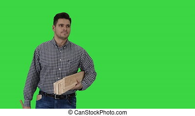 Brunette man builder with planks is ready to build something on a Green Screen, Chroma Key.