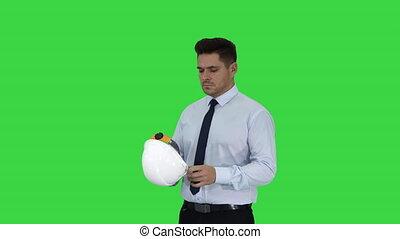 Businessman putting hardhat helmet on Safety on a Green...