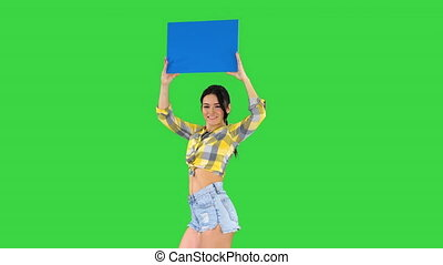 Medium shot. Walking in and out of the frame. Girl with an empty board announcing new round on a Green Screen, Chroma Key. Professional shot in 4K resolution. 021. You can use it e.g. in your commercial video, business, presentation, broadcast