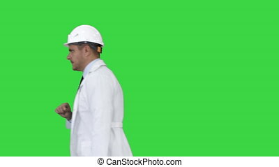 Portrait of architect wearing hardhat looking at watch like...