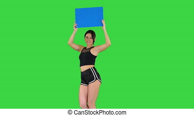 Medium shot. Walking in and out of the frame. Ring girl walking holding empty board presenting new round on a Green Screen, Chroma Key. Professional shot in 4K resolution. 021. You can use it e.g. in your commercial video, business, presentation, broadcast