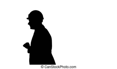 Silhouette Portrait of architect wearing hardhat looking at...