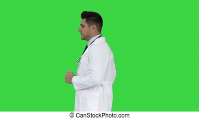 Walking male doctor passing by on a Green Screen, Chroma Key.