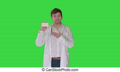 Medium shot. Walking Male Doctor showing empty white box of pills on a Green Screen, Chroma Key. Professional shot in 4K resolution. 4151. You can use it e.g. in your commercial video, business, presentation, broadcast