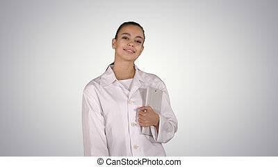 Woman doctor walking with tablet in hands on gradient background.