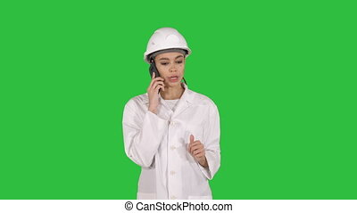 Woman engineer talking on the phone while walking on a Green Screen, Chroma Key.
