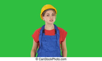 Woman in construction outfit talking to camera while walking on a Green Screen, Chroma Key.