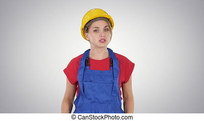 Woman in construction outfit talking to camera while walking on gradient background.