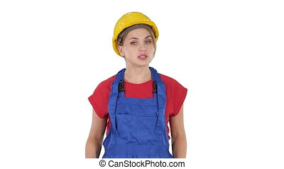 Woman in construction outfit talking to camera while walking on white background.