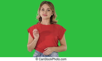 Woman presenting product with her hand showing to side on a Green Screen, Chroma Key.