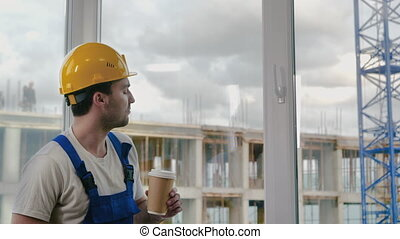 Medium shot. Worker wearing hardhat taking a break drinking coffee. Professional shot in 4K resolution. 025. You can use it e.g. in your commercial video, medical, business, presentation, broadcast