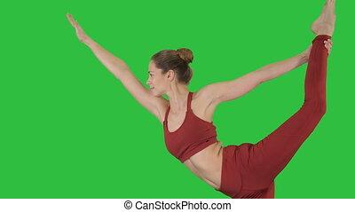 Yoga teacher practising pose dandayamana dhanurasana on a...