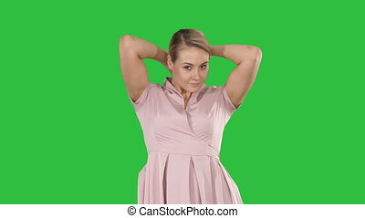 Young beautiful woman primp to the camera smiling on a Green Screen, Chroma Key.