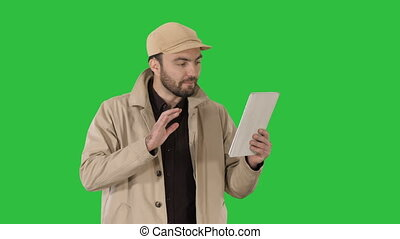 Young businessman using digital tablet making video call on a Green Screen, Chroma Key.