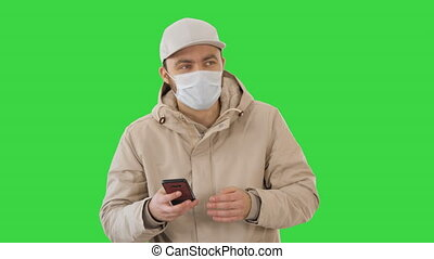 Medium shot. Young casual man walking making a call wearing warm clothes and protective mask on a Green Screen, Chroma Key. Professional shot in 4K resolution. 53. You can use it e.g. in your medical, commercial video, business, presentation, broadcast