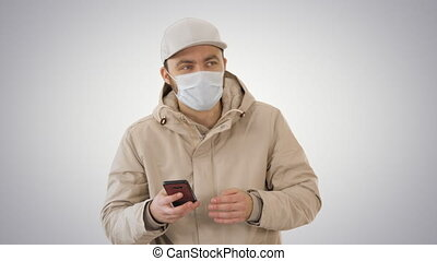 Young casual man walking making a call wearing warm clothes and protective mask on gradient background.